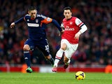 Mesut Ozil of Arsenal holds off Clint Dempsey of Fulham during the Barclays Premier League match between Arsenal and Fulham at Emirates Stadium on January 18, 2014