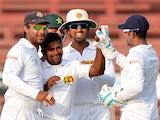 Sri Lanka's Rangana Herath celebrates with teammates after the dismissal of Pakistani batsman Ahmed Shehzad on January 18, 2014