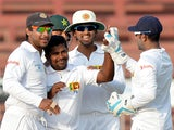 Sri Lanka's Rangana Herath celebrates with teammates after the dismissal of Pakistani batsman Ahmed Shehzad on January 18, 2014