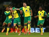 Leroy Fer and Russell Martin of Norwich City congratulate Ryan Bennett of Norwich City on scoring their first goal during the Barclays Premier League match against Hull City on January 18, 2014