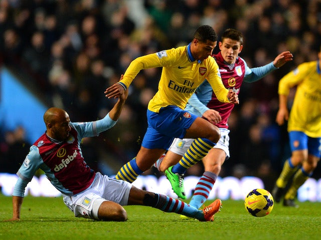 Fabian Delph of Aston Villa tackles Serge Gnabry of Arsenal during the Barclays Premier League match between Aston Villa and Arsenal at Villa Park on January 13, 2014