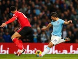 Sergio Aguero of Manchester City shoots past Steven Caulker of Cardiff to score his team's fourth goal during the Barclays Premier League match on January 18, 2014