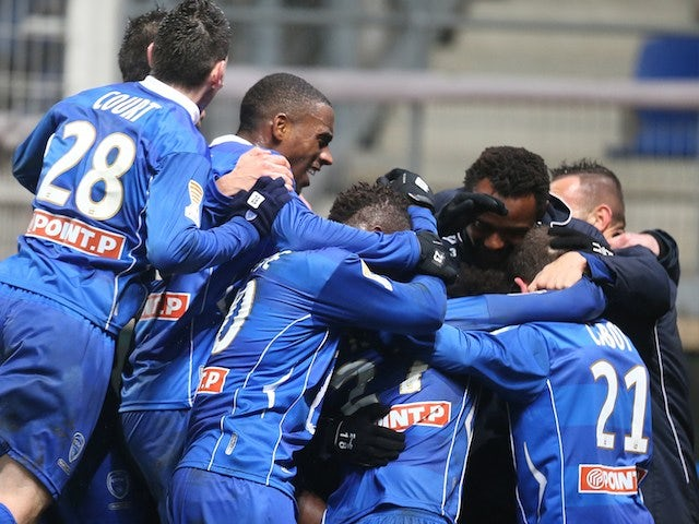 Troyes' players celebrate after winning the French League Cup quarter final football match Troyes vs Evian, on January 15, 2014