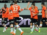 Lorient's French midfielder Yann Jouffre (R) celebrates with his teammates after scoring a goal during the French L1 football match between Lorient and Guingamp on January 18, 2014