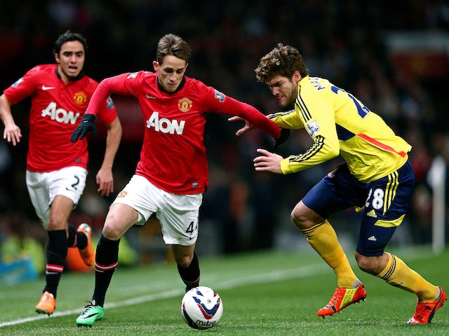 Adnan Januzaj of Manchester United is challenged by Marcos Alonso of Sunderland during the Capital One Cup semi final, second leg match on January 22, 2014
