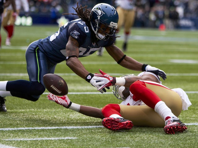 Wide receiver Michael Crabtree #15 of the San Francisco 49ers reaches for the ball as Richard Sherman #25 of the Seattle Seahawks dives in at CenturyLink Field December 24, 2011