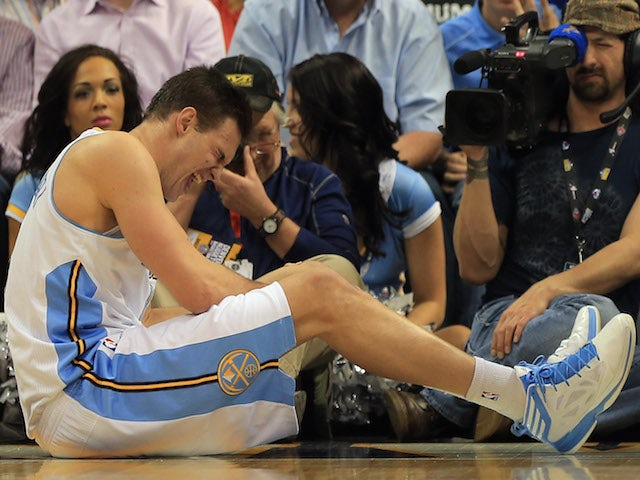 Danilo Gallinari of the Denver Nuggets grimaces as he injures his left leg and was forced to leave the game against the Dallas Mavericks at the Pepsi Center on April 4, 2013