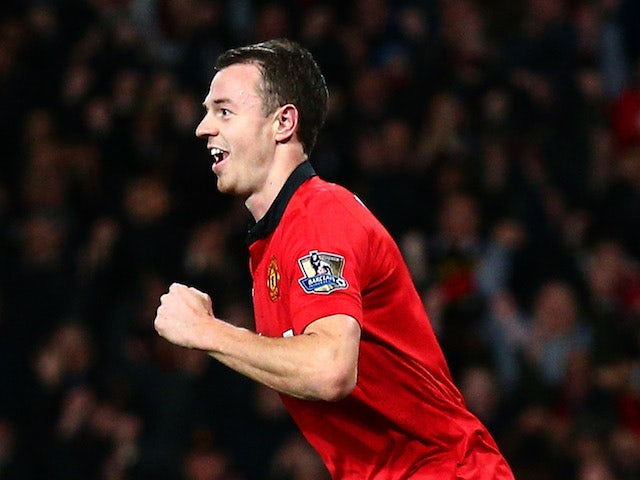 Jonny Evans of Manchester United celebrates after scoring the opening goal as a dejected John O'Shea of Sunderland looks on during the Capital One Cup semi final on January 22, 2014