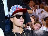 Singer Justin Bieber sits courtside as he watches the Miami Heat host the Indiana Pacers during Game Seven of the Eastern Conference Finals of the 2013 NBA Playoffs at AmericanAirlines Arena on June 3, 2013