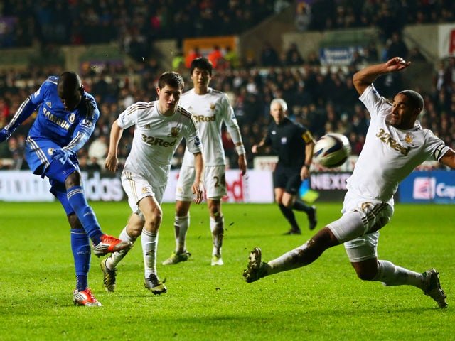 Demba Ba of Chelsea shoots past Ashley Williams of Swansea City during the Capital One Cup Semi-Final Second Leg match between Swansea City and Chelsea at Liberty Stadium on January 23, 2013