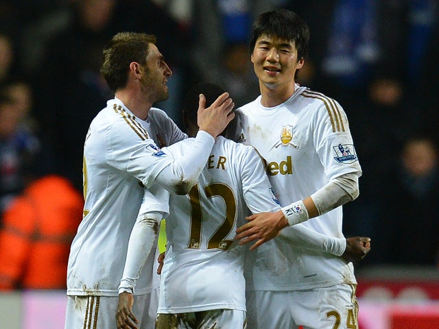 Swansea City's South Korean midfielder Ki Sung-Yueng celebrates with Swansea City's Spanish defender Angel Rangel and Swansea's English forward Nathan Dyer at the final whistle of the English League Cup semi-final second leg football match between Swansea