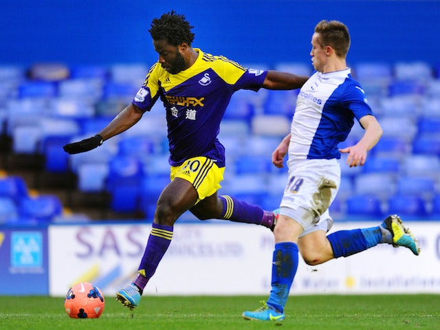 Wilfried Bony of Swansea shoots past Mitch Hancox of Birmingham during the FA Cup fourth round match on January 25, 2014