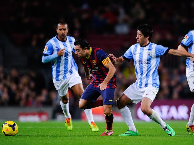 Xavi Hernandez of FC Barcelona duels for the ball with Pablo Perez of Malaga CF during the La Liga match between FC Barcelona and Malaga CF at Camp Nou on January 26, 2014