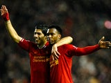 Daniel Sturridge of Liverpool is congratulated by teammate Luis Suarez after scoring his team's third goal during the Barclays Premier League match between Liverpool and Everton at Anfield on January 28, 2014