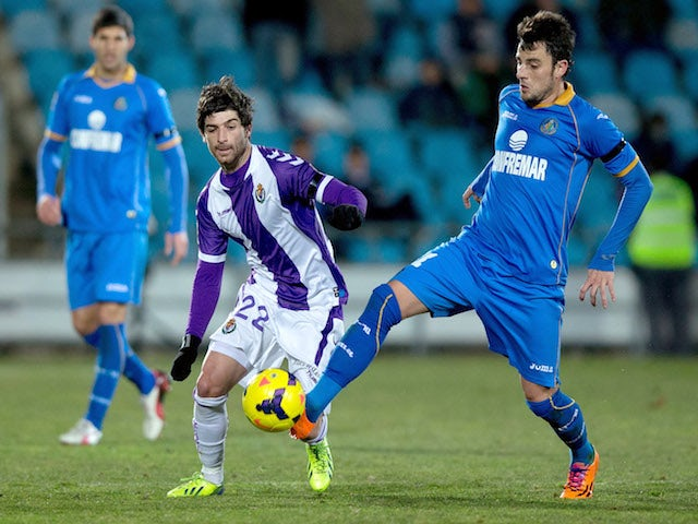 Miguel Marcos alias Michel (R) of Getafe CF competes for the ball with Victor Perez (L) of Real Valladolid CF during the La Liga match on February 1, 2014