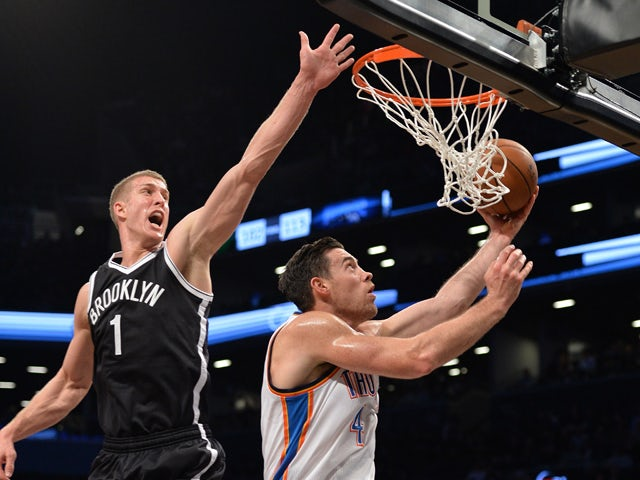 Nick Collison of the Oklahoma City Thunder drives against Mason Plumlee of the Brooklyn Nets during their NBA game January 31, 2014