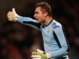 Real Betis goalkeeper Stephan Andersen shouts to his players during the UEFA Europa League Group I match between Olympique Lyonnais and Real Betis Balompie at Stade de Gerland on November 28, 2013