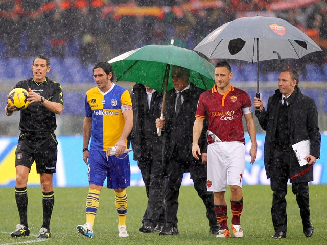 The referee Andrea De Marco with Alessandro Lucarelli of Parma FC and Francesco Totti of AS Roma check the field condition during the Serie A match between AS Roma and Parma FC at Stadio Olimpico on February 2, 2014