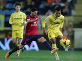 Osasuna's Cristian Lobato Villegas and Villarreal's Ikechukwu Uche in action during their La Liga match on February 3, 2014
