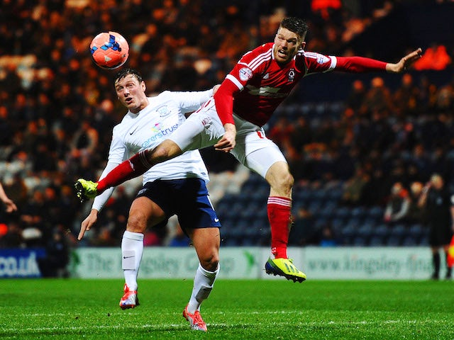 Lee Holmes (L) of Preston North End and Jamie Mackie (R) of Nottingham Forest challenge for the ball during the FA Cup Fourth Round Replay match on February 5, 2014