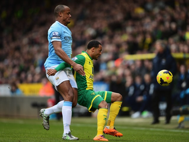 Nathan Redmond of Norwich City holds off the challenge of Vincent Kompany of Manchester City during the Barclays Premier League match between Norwich City and Manchester City at Carrow Road on February 8, 2014