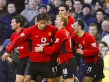 Man United's Ruud Van Nistelrooy celebrates with teammates after scoring his team's fourth goal against Everton during their Premier League match on February 7, 2004
