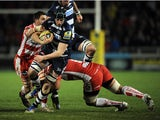 James Gaskell of Sale Sharks is tackled by Sione Kalamafoni of Gloucester during the Aviva Premiership match between Sale Sharks and Gloucester at the AJ Bell Stadium on February 07, 2014
