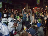 Seattle Seahawks fans including Lynnsey Sturgeon (C) react while watching their team play the Denver Broncos in the Super Bowl at 95 Slide, a sports bar in Seattle on February 2, 2014
