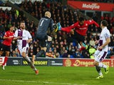 Fraizer Campbell of Cardiff City challenges Bradley Guzan the Aston Villa goalkeeper during the Barclays Premier League match between Cardiff City and Aston Villa at Cardiff City Stadium on February 11, 2014