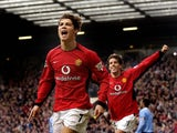 Manchester United's Cristian Ronaldo (L) celebrates after scoring his team's third goal as teammate Ruud Van Nistelrooy (R) runs behind him on February 14, 2004