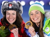 Gold medalists Switzerland's Dominique Gisin and Slovenia's Tina Maze pose on the podium during the Women's Alpine Skiing Downhill Medal Ceremony at the Sochi medals plaza during the Sochi Winter Olympics on February 12, 2014