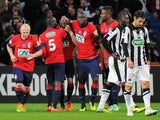 Lille's French forward Nolan Roux is congratulated by his teammates after scoring a goal during the French Cup football match Lille vs Caen on February 11, 2014