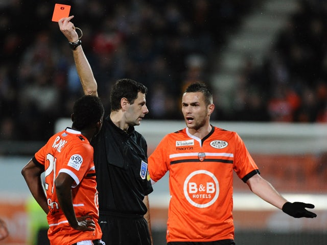 French referee Alexandre Castro gives a red card to Lorient's French midfielder Alain Traore during the French L1 football match between Lorient and Toulouse on February 15, 2014