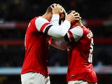 Arsenal's Lukas Podolski celebrates scoring with team mate Alex Oxlade-Chamberlain against Liverpool during their FA Cup fifth round match on February 9, 2014