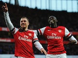 Arsenal's Lukas Podolski celebrates scoring with team mate Yaya Sanogo against Liverpool during their FA Cup fifth round match on February 9, 2014
