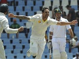 Australia cricketer Mitchell Johnson celebrates with team-mates after taking a wicket of South Africa's Alviro Petersen, during the 4th day of the first test match on February 15, 2014