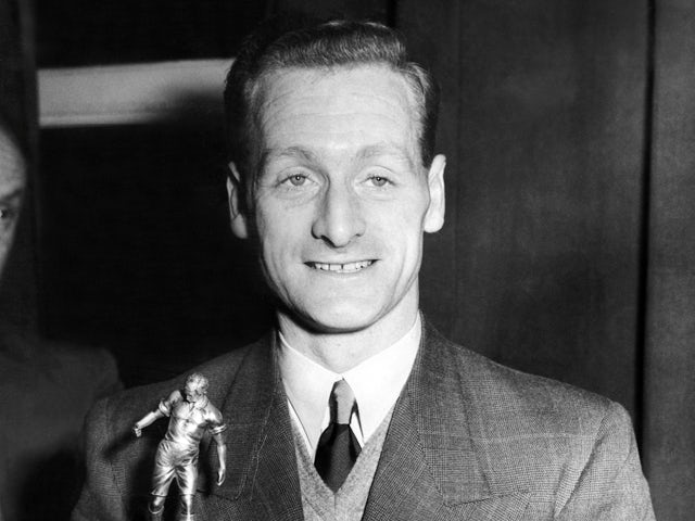 Preston North End's forward Tom Finney smiles as he holds his trophy in London after being elected the Footballer of the Year by the Football Writers Association on 29 April, 1954