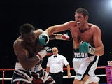 Tyson Fury throws a punch at Dereck Chisora during the British & Commonwealth Heavyweight Title Fight between Dereck Chisora and Tyson Fury at Wembley Arena on July 23, 2011