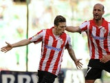 Athletic Bilbao's forward Iker Muniain celebrates with midfielder Benat Etxebarria Urkiaga after scoring during the Spanish league football match Real Betis Balompie vs Athletic Club Bilbao at the Benito Villamarin stadium in Sevilla on February 23, 2014