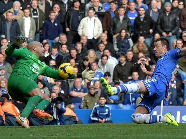 Chelsea's English defender John Terry lunges toward the ball as Everton's US goalkeeper Tim Howard fails to make the save leading to the winning goal from a free kick by Chelsea's English midfielder Frank Lampard during the English Premier League football