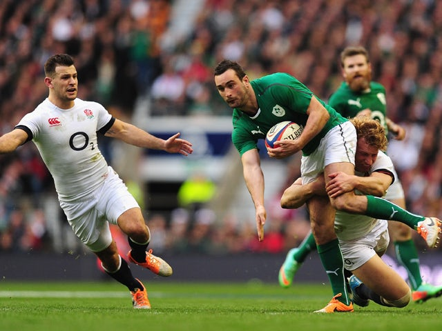 Ireland wing Dave Kearney is tackled by Billy Twelvetrees as Danny Care looks on during the RBS Six Nations match between England and Ireland at Twickenham Stadium on February 22, 2014