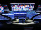 National flags are seen on a giant screen as Dutch former football star Ruud Gullit and French Bixente Lizarazu presents the qualifying draw Euro 2016, on February 23, 2014