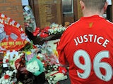 A Liverpool football club supporter looks at floral tributes and memorabilia ahead of a memorial service to mark the twentieth anniversary of the Hillsborough disaster at Anfield in Liverpool, north-west England on April 15, 2009