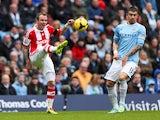 Glenn Whelan of Stoke City shoots past Aleksandar Kolarov of Manchester City during the Barclays Premier League match between Manchester City and Stoke City at the Etihad Stadium on February 22, 2014