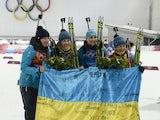 Gold medalists Ukraine's Vita Semerenko, Juliya Dzhyma, Olena Pidhrushna and Valj Semerenko celebrate during the Women's Biathlon 4x6 km Relay Flower Ceremony at the Laura Cross-Country Ski and Biathlon Center during the Sochi Winter Olympics on February