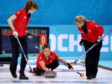 Vicki Adams of Great Britain (C) plays a stone as Claire Hamilton (L) and Anna Sloan (R) assist during the Bronze medal match against Switzerland on February 20, 2014