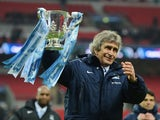 Manuel Pellegrini, manager of Manchester City celebrates victory with the trophy after the Capital One Cup Final between Manchester City and Sunderland at Wembley Stadium on March 2, 2014