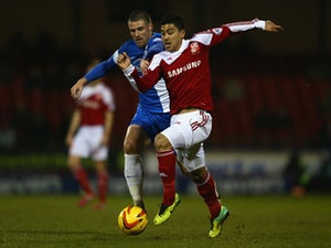 Massimo Luongo of Swindon Town is challenged by Michael Bostwick of Peterborough United during the Johnstone's Paint Southern Area Final Second Leg match between Swindon Town and Peterborough United at the County Ground on February 17, 2014