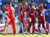 West Indies bowler Sunil Narine celebrates after taking the wicket of English batsman Joe Root during the first One Day International match bewteen West Indies and England at the Sir Vivian Richard Stadium in St John's on February 28, 2014