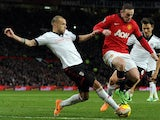 Fulham's Dutch defender John Heitinga closes in on Manchester United's English striker Wayne Rooney during the English Premier League football match between Manchester United and Fulham at Old Trafford in Manchester on February 9, 2014